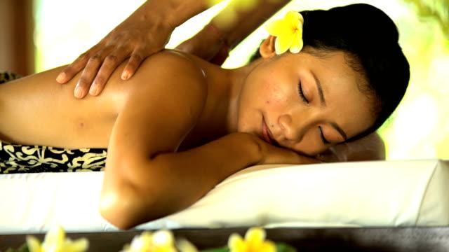 therapeutic massage by masseuse at tropical spa bali - spa treatment点の映像素材/bロール