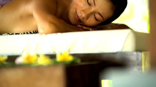 therapeutic massage treatment at tropical spa resort bali - spa treatment点の映像素材/bロール