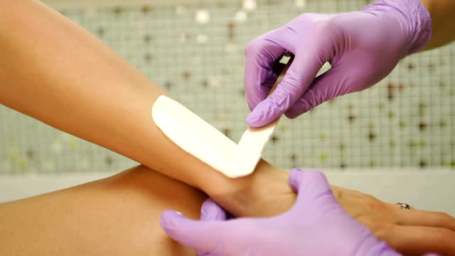 therapist applying wax on woman forearm - forearm stock videos and b-roll footage