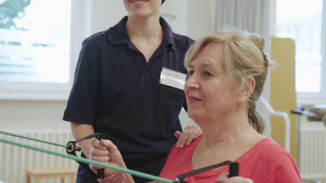 therapist assisting woman with resistance band - physiotherapy stock videos & royalty-free footage