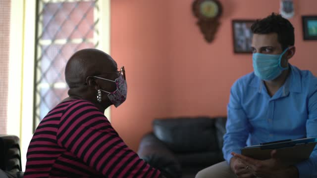 therapist counsels senior woman at home (or surveyor) - wearing face mask - mental health professional stock videos & royalty-free footage