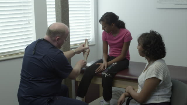 Therapist explaining knee function to teenage girl and mother.