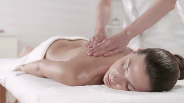 hd: therapist massaging young woman in spa center - massage table stock videos & royalty-free footage
