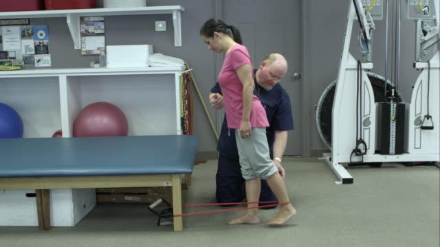 vídeos y material grabado en eventos de stock de therapist working with woman for elastic band exercises. - articulación humana