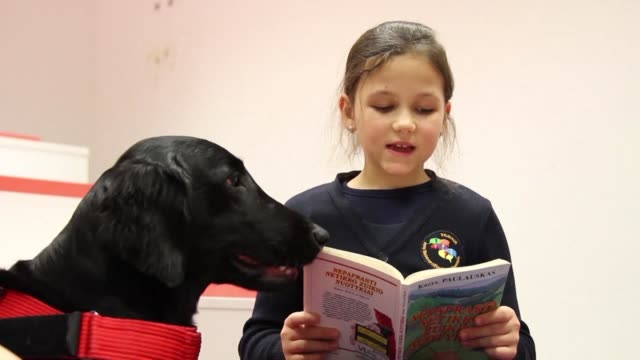 Therapy dogs give struggling young readers in Lithuania the positive attention and confidence they need to become happy bookworms