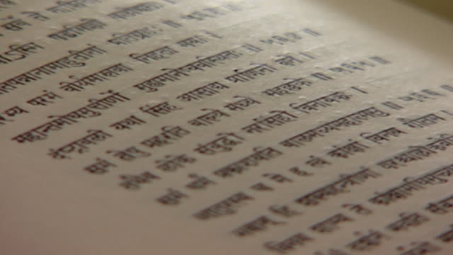 vidéos et rushes de theravada buddhism. side view of a section of a page containing a buddhist text in sanskrit. - lettre de l'alphabet