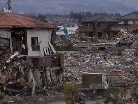 there is an opening medium panning shot of an area completely wiped out and filled with debris. there is a dissolve to a medium shot of damaged homes... - earthquake stock videos & royalty-free footage