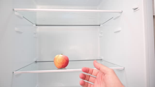 vídeos de stock e filmes b-roll de there is only one apple in the empty refrigerator. a man's hand shows it. - crise mundial de alimentos