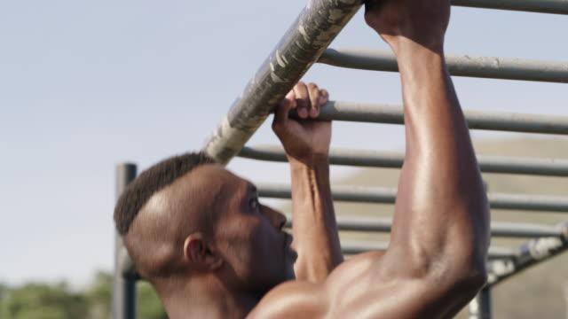 vídeos de stock e filmes b-roll de there's power in his arms - equipamento de parque infantil