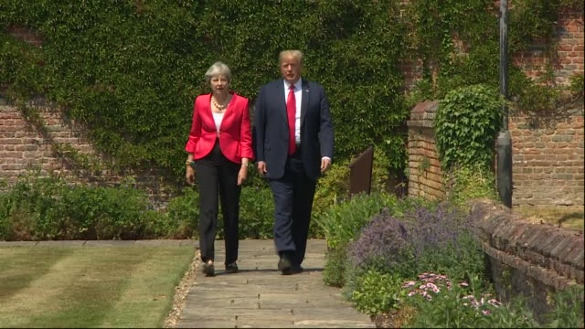 Theresa May and Donald Trump walking through the grounds of Chequers during the President's visit to the UK