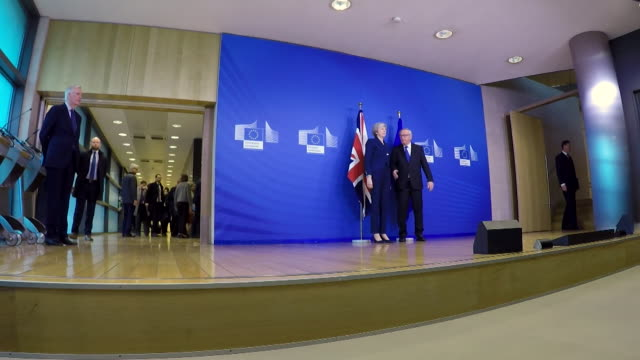 Theresa May and Jean Claude Junker shake hands at photocall at EU in Brussels during visit to discuss Brexit withdrawal agreement