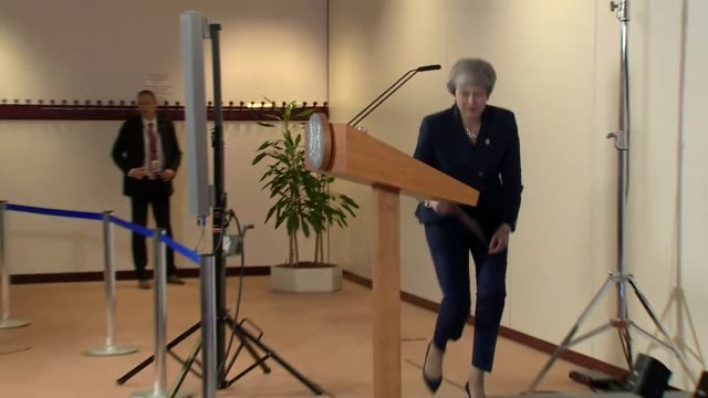 Theresa May approaching the lectern and saying 'good morning' during an EU Summit in Brussels