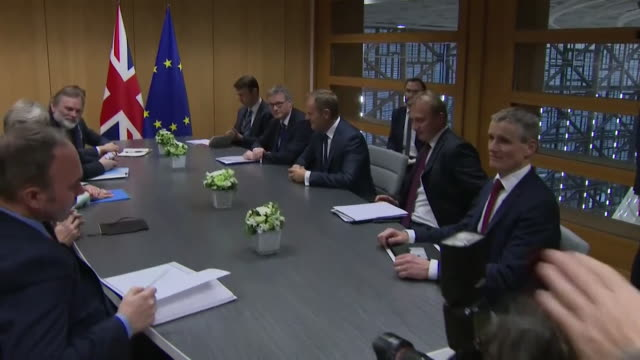 Theresa May at a table with Donald Tusk in the EU Parliament building