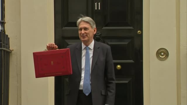 theresa may faces conservative unrest over defence cuts london downing street photography*** philip hammond mp holding up red budget box - 予算点の映像素材/bロール