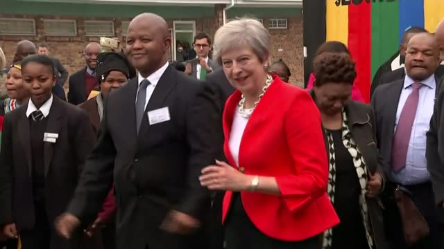 theresa may pledges £4 billion of extra investment to africa as threeday trade mission begins south africa cape town theresa may dancing at school... - theresa may stock videos & royalty-free footage