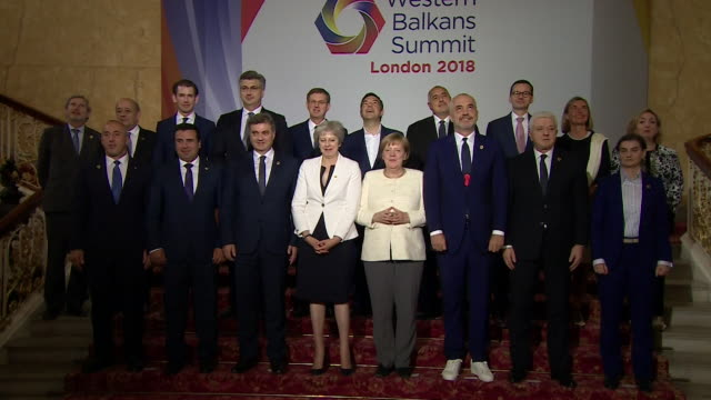 theresa may posing for a group photograph with angela merkel and western balkans leaders at the western balkans summit in london - europäische union stock-videos und b-roll-filmmaterial