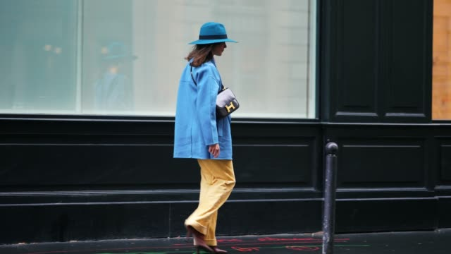 therese hellström wears a blue hat, a white ruffled shirt, a blue oversized blazer jacket, a hermes bag, pale yellow corduroy pants, brown pointy... - paris fashion week stock videos & royalty-free footage