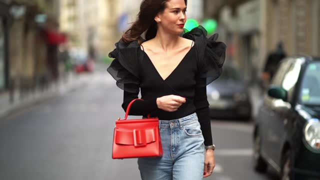 therese hellström wears earrings a black lowneck vneck top with mesh ruffled puff shoulders blue denim jeans a red leather bag pointy bejeweled... - v neck stock videos & royalty-free footage