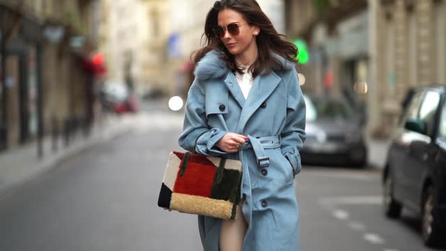vídeos y material grabado en eventos de stock de therese hellström wears sunglasses, a blue long winter wool trench coat with fluffy faux fur collar, white pants, a fluffy red and green khaki bag,... - abrigo