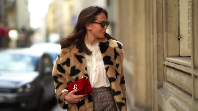 vídeos y material grabado en eventos de stock de therese hellström wears sunglasses, earrings, a pale brown / beige fluffy faux fur coat with printed black hearts, a white ruffled mesh pleated shirt... - abrigo
