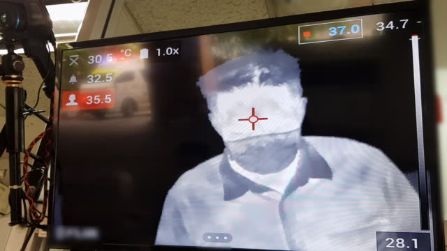 thermal scanning temperature of asian man at shopping mall or airport to prevention of covid-19 corona virus pandemic - thermal imaging stock videos & royalty-free footage