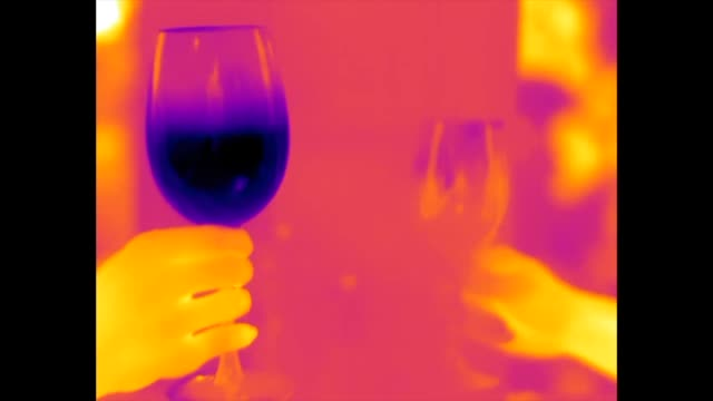 thermal video of a glass of chilled white wine (on the left) and a glass of room temperature red wine (on the right) being clinked together in a toast - thermal imaging stock videos & royalty-free footage