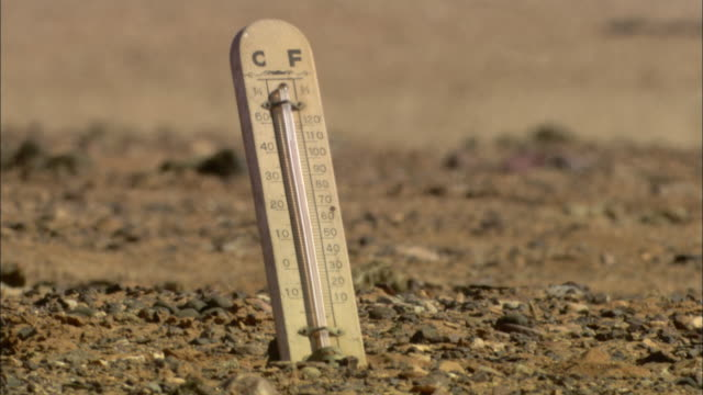 vidéos et rushes de a thermometer in the desert displays a high temperature. - température