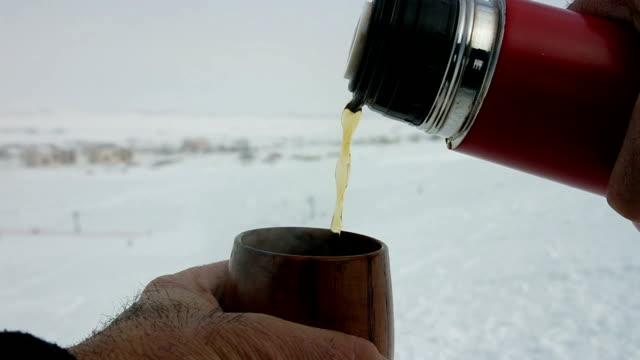 Thermos té y una pequeña taza de té en la pista de esquí