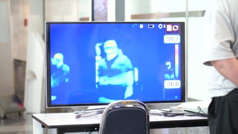 stockvideo's en b-roll-footage met thermoscan monitoring scannen mensen op koorts - autoriteit