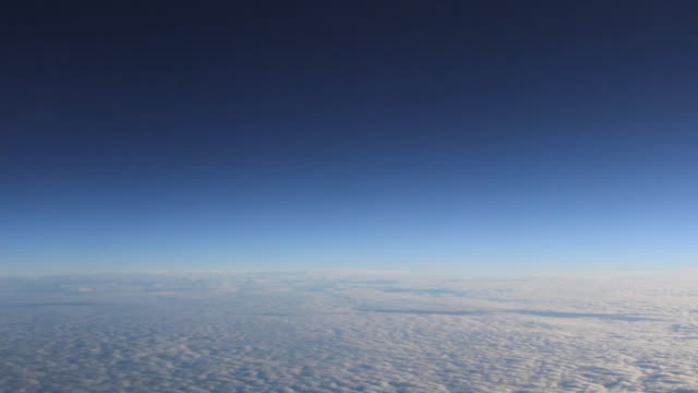 AERIAL A thick cloud deck and dark blue skies over horizon