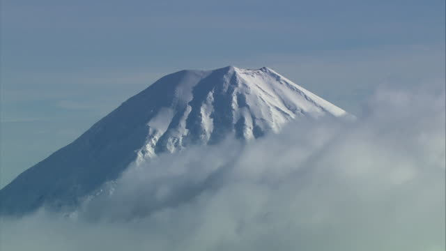 aerial thick clouds blanketing the base and rising to the peak of snow-covered mount ngauruhoe / manawatu-wanganui, new zealand - tongariro national park stock videos & royalty-free footage