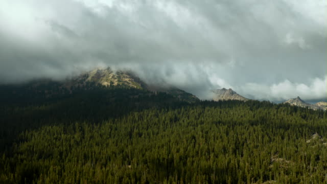 thick clouds hover over mountain peaks in lassen volcanic national park, northern california. - wildnis stock-videos und b-roll-filmmaterial