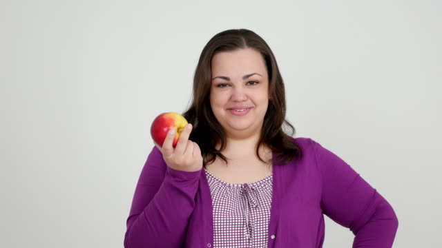 thick girl eating an apple on a white background - 25 29 years stock videos and b-roll footage