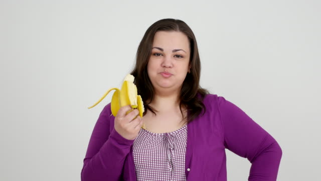 thick girl eating banana and showing thumb - banana stock videos and b-roll footage