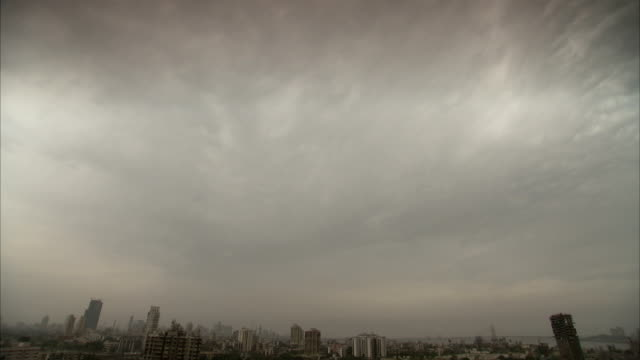thick gray clouds fill the sky above the dharavi area of mumbai. - population explosion stock videos & royalty-free footage