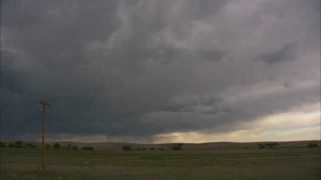 thick gray storm clouds rain over a green field. - storm cloud stock videos & royalty-free footage