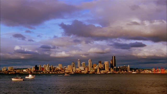 thick grey clouds create shadows on elliot bay. - washington mutual tower stock videos & royalty-free footage