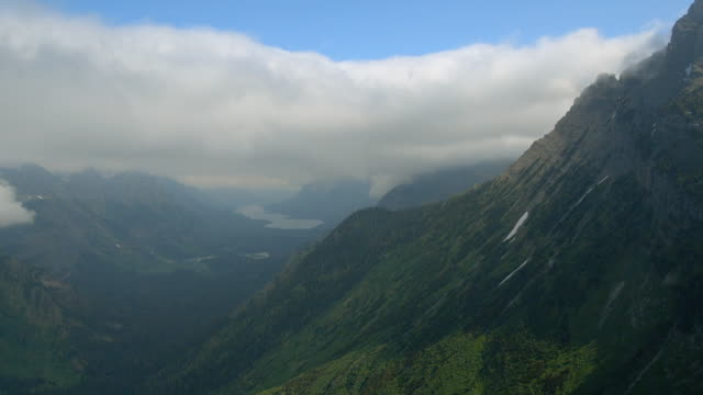 A thick layer of clouds hangs over a mountain valley in Glacier National Park.