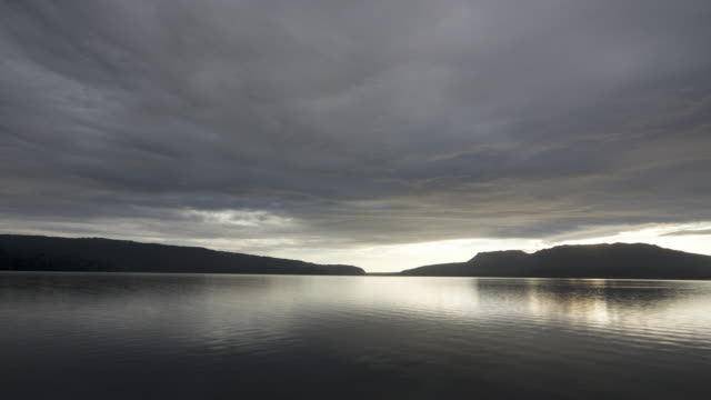 A thick layer of clouds passes over a jetty on Lake Tarawera in New Zealand.
