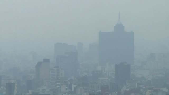 thick layer of smog envelops mexico city which has declared an air pollution alert for the second straight day urging people to stay indoors... - smog stock videos & royalty-free footage