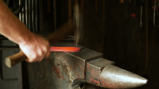 vídeos de stock e filmes b-roll de thick metal object hit with hammer on anvil - ferro metal