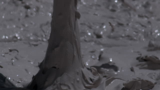Thick mud bubbles and spatters in mud pot geyser.