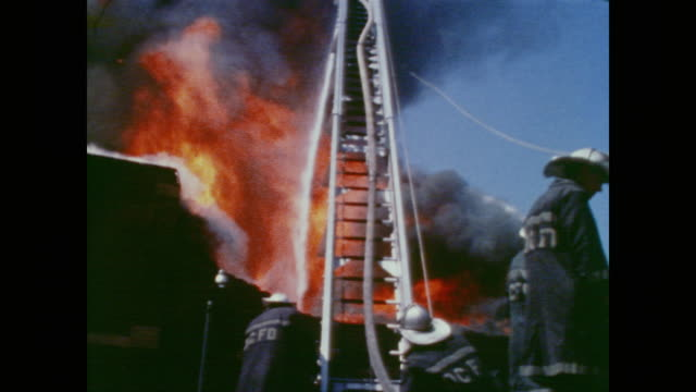 thick smokes pours from a burning building as firefighters with ladders and hoses try their best to manage the situation as flames begin to roar out... - 1968 stock videos & royalty-free footage