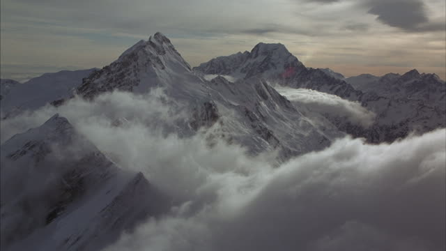 thick snow-clouds blow over a tall ridge in a vast snow-covered mountain range. - thick stock videos & royalty-free footage