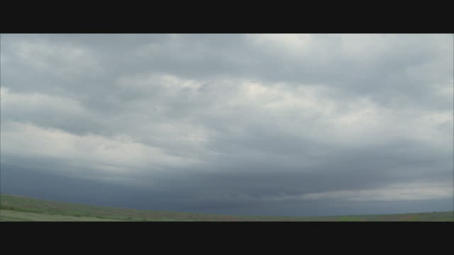 vidéos et rushes de ws, thick storm clouds gathering over field  - orage