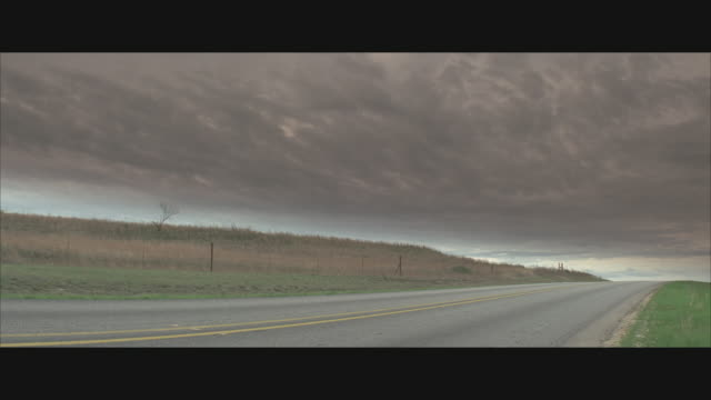 ms, thick stormy clouds over rural highway - anamorphic stock videos and b-roll footage