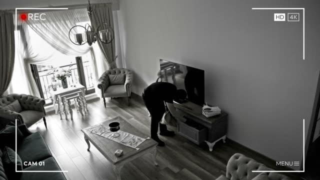 vídeos de stock, filmes e b-roll de ladrão que olha a câmera de segurança em uma casa - definição 4k - roubando crime