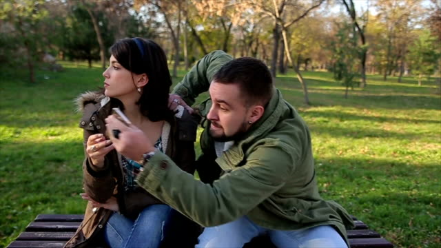 thief stealing a mobile phone to a woman sitting on a bench in a park - thief stock videos & royalty-free footage