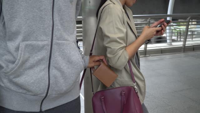 vídeos de stock e filmes b-roll de thief stealing smart phone from traveler woman - bandido