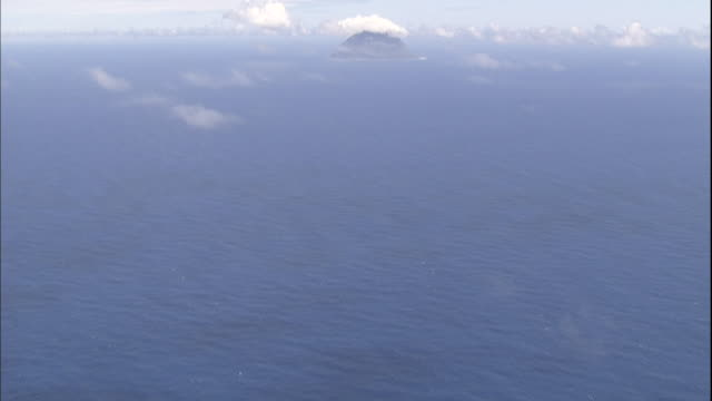 thin clouds float over the pacific ocean and kita iwo jima island. - iwo jima island stock videos and b-roll footage